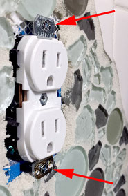 White double plug outlet with two screws in a backsplash