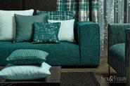 Eine Couch mit vielen Kissen, alles in türkis gehalten