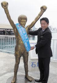具志堅用高氏の銅像に国際ボクシング殿堂入りを記念してタスキを掛ける中山市長=25日午後、石垣港離島ターミナル