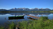 Am idyllischen Hopfensee mit einem Ruderboot und blick auf die Alpen