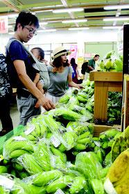青々とした島バナナを手に取って品定めする観光客=15日午後、JAファーマーズマーケットゆらてぃく市場