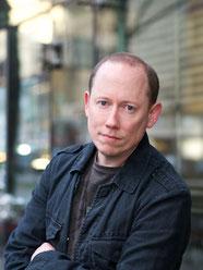 Buchautor Klaus Oppitz blickt ernst in die Kamera.