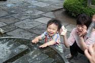 祐希は仏足石に溜まった雨水を手でバチャバチャするのが大好き。服はビショビショになるが楽しくて仕方がない様子。