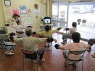 ▲介護福祉センターに集まって「いきいき百歳体操」をする地域の高齢者の皆さん(手首に重りの入ったベルトを巻いています)