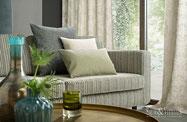 Ein Sofa mit Kissen und Gardinen am Fenster, alles in grün, grau und weiß gehalten