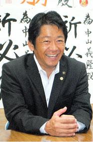 当選から一夜明け、笑顔で報道陣のインタビューに応じる中山氏=3日午前8時ごろ、自民党事務所