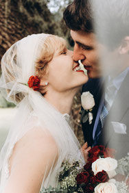 Eine Braut mit Brautfrisur mit Schleier, hier eine weiße, sogenannte Bridal Cap, ist im Begriff ihren Ehemann zu küssen.