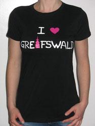 I love Greifswald-Damenshirt, schwarz (Stella) mit weißer Schrift und pinkem Herz/Turm.
