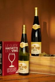 Een fles Elzas Pinot Noir en een fles Elzas Pinot Blanc op een kist met de wijngids