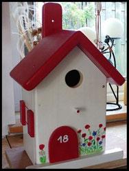 Houten nestkastje, rood dak en zomerbloemen, vrolijk leuk vogelhuisje