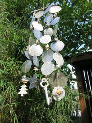 Windspiel aus weißen und grauen Capiz Muscheln - vor hellgrünem Bambus.
