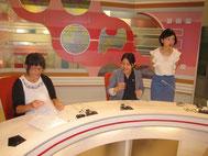 キャスター体験。左が生徒。中央がプロデューサー。右が菅久キャスター。