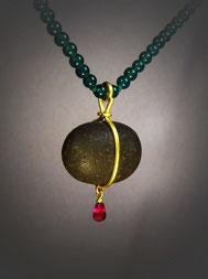 Perfekt natürlich geformter Kieselstein mit Golddraht gefaßt, hängt er an feiner grüner Kugelkette. Unterhalb am Draht baumelt ein roter Rubintropfen.