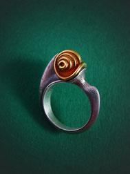 Organisch geformter Silberring mit einem schneckenartig geformten Ringkopf.