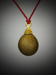 Natürlicher perfekt eiförmiger gelbbrauner Kieselstein mit einer dreistufigen Goldkappe als Angänger an roter Kordel.