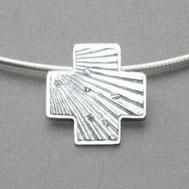 Bild: gleichschenkliges Kreuz mit Oberfläche einer Jacobsmuschel , 6 kleine Diamanten funkeln auf die Oberfläche, Schmuckbrise Goldschmiede Hildebrandt Flensburg
