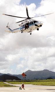 つり上げ訓練で、救助者を抱えヘリコプターへ戻る機動救難士=15日午後、第11管区海上保安本部石垣航空基地