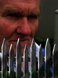 grimmiger Mann hinterm Zaun