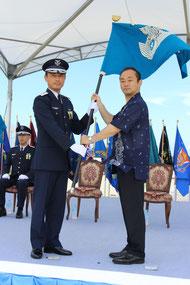 武藤空将(中央)に宮澤政務官から指揮官旗が授与された=1日 航空自衛隊那覇基地