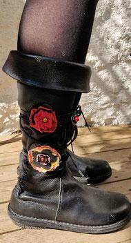 Deux fleurs de bottes dans les tons rouges portée sur des bottes.