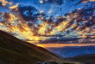Vaste ciel au soleil couchant, mer de nuages derrière un versant de montagne