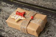Un cadeau emballé et ficelé par une petite corde plate avec une étoile rouge et blanche accrochée