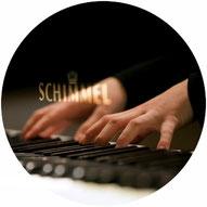 Hände am Klavier die Tasten anschlagen