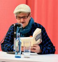 Litt Leweir (bei einer Buchmesse-Lesung, mit Mikrofon und Wasserflasche)