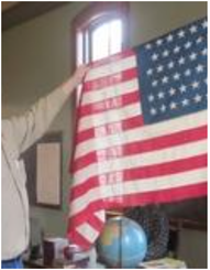 Local historian Kit Karsten displays a 46-star American flag at the New Groningen Schoolhouse in Holland Township.