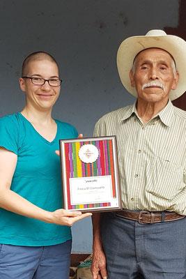 """2016  Don Agapito gibt seine Plakete für den 1. Platz bei dem Wettbewerb von Anacafé der Region  """"San Marcos"""" an Quijote Kaffee, damit wir zeigen können, was für tollen Kaffee sie produzieren"""