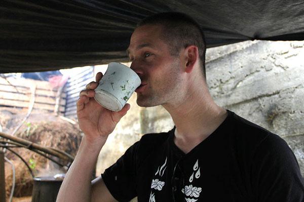Pingo trinkt Zuckerrohrschnaps direkt aus der Destille eines AACRI-Farmers