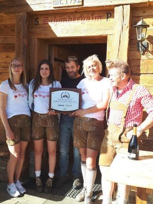 Die Wirtsfamilie Seeber präsentiert stolz die Auszeichnung zur beliebtesten Almhütte Südtirols (2. Platz)