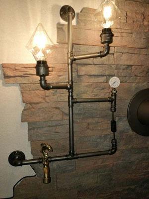Perfekt eingefügt ist diese individuell gestaltete Rohrlampe mit sandgestrahlten schwarzen Stahlrohren. Die Zuleitung kommt aus der Wand und wird vom Flansch überdeckt.   (c) T. Stacke