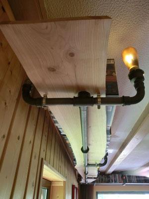 Von der Decke abgehängtes umlaufendes Bücherregal aus stabilem Stahlrohr. Beleuchtung integriert. | (c) S. Erb