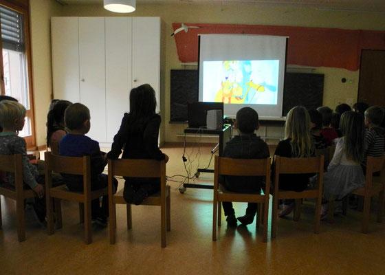 Die DaZ-Lehrerin, Frau Gartmann, richtet ein Kino ein, während die beiden Kindergärtnerinnen das Nötigste am neuen Ort vorbereiten.