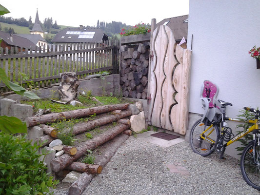 Ein Gartentor das nicht nur den Weg versperrt, sondern zum Verweilen einlädt.