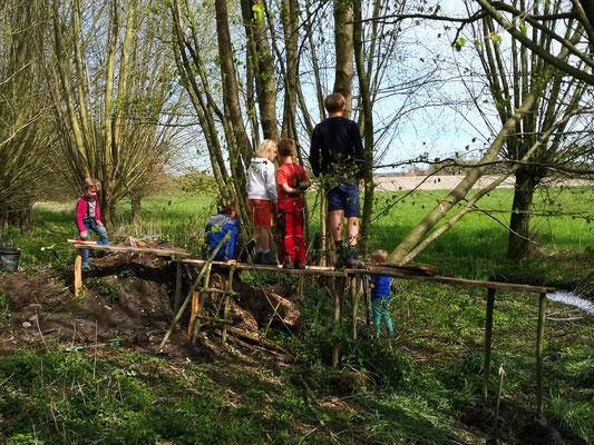 Kinder bauen eine Holzbrücke