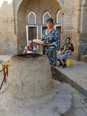 Frauen backen und verzieren das Brot mit Stempeln