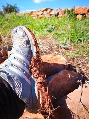 Die Lehmerde klebt an den Schuhen