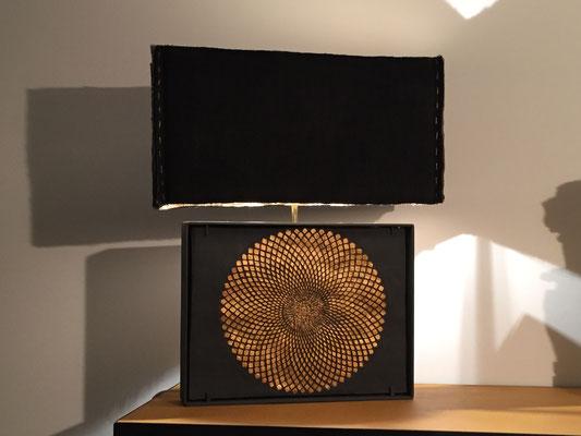 création originale d'une lampe composée d'un cadre en métal peint en noir, à l'intérieur bas relief en argile, abat jour en tissus.