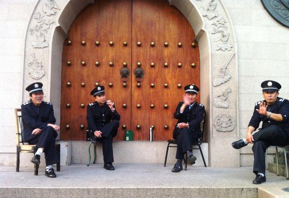 Vier rauchende Uniformierte in Shanghai, die dann doch nicht fotografiert werden wollten