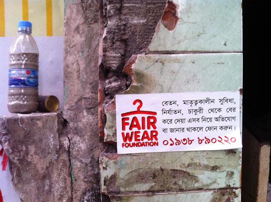 Ein Aufkleber der Fair Wear Foundation an der Wand des Gewerkschaftsbüros NGWF in Dhaka