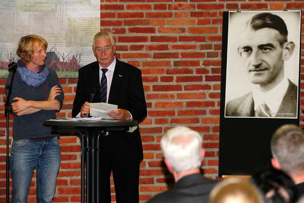 Dolf Hamming aus den Niederlanden (verst. am 12. Juli 2017) bei der Gedenkveranstaltung 2014 in Engerhafe. Rechts das Foto seines Vaters, Jacob Lodewijk Hamming, der 1944 im Außenlager KZ Engerhafe umgebracht wurde.