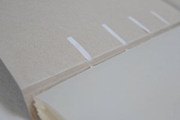 Fixation des supports de couture sur une reliure de conservation en papier fait main.