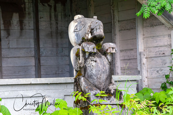 Old House in Icy Strait Point in Glacier Bay, Alaska with a wooden bear sculpture in front.