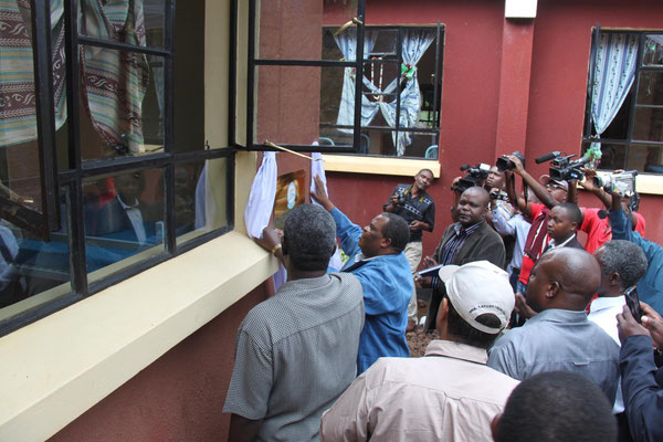 The commissioner unwrap the information plate at the building. The two extensions to the girls dormitory were financed by TANAPA and KINAPA.