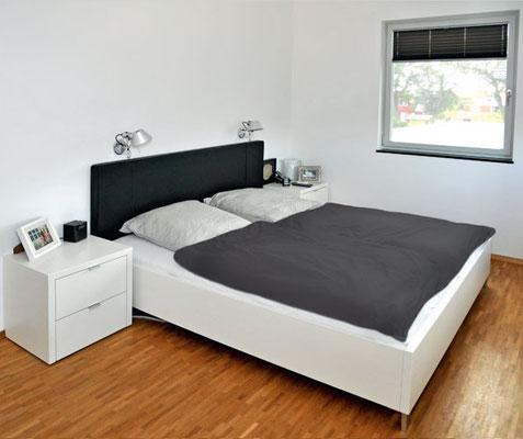 Tischlerei Vöge - Individuell gestaltetes Schlafzimmer. Weiß lackiertes Bett mit Leder-Kopfteil und passenden Nachtschränken.