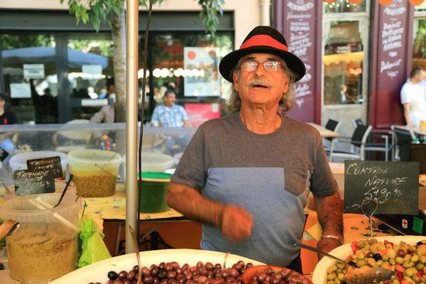 Zyczliwy kupiec na targowisku oferuje oliwki