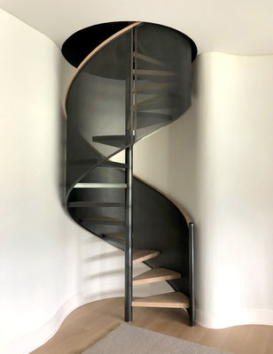 Patinated steel spiral staircase with wood cup handrail and step for a private residence - Hamptons