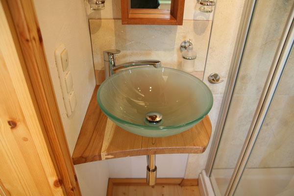 Das Glaswaschbecken harmoniert mit der Platte aus gestockter Buche